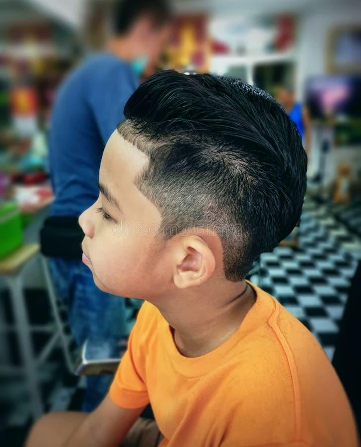 Asian Boy Wearing T-Shirt Getting New Hair Cut at Barber Shop stock image