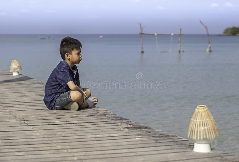 Asian boy on the wooden bridge pier boat in the sea and the bright sky at Koh Kood, Trat in Thailand.  stock images