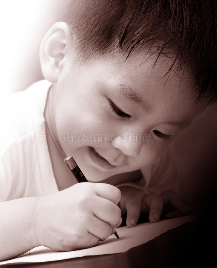 Asian boy writing on paper stock images