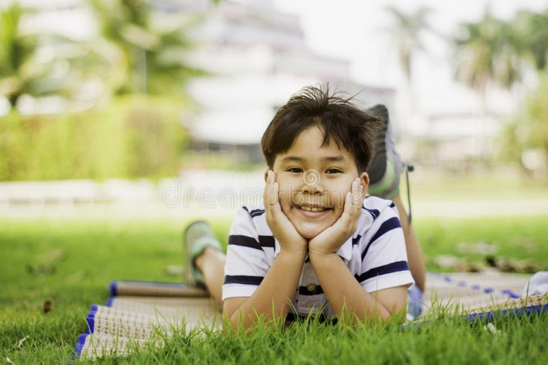 Asian boys are in the mood to relax on weekends in the park in the morning sunshine,concept of bright childhood, learning outside. The classroom and finding stock image