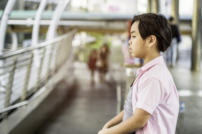 Asian boys sit stress and bad mood alone in the open space of the school, the concept of being bullied Cynicism and racism.  stock photography