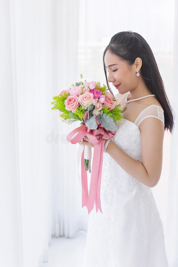 An Asian bride dressed in a white wedding dress stands smiling brightly in a hand holding a beautiful flower bouquet.  stock image