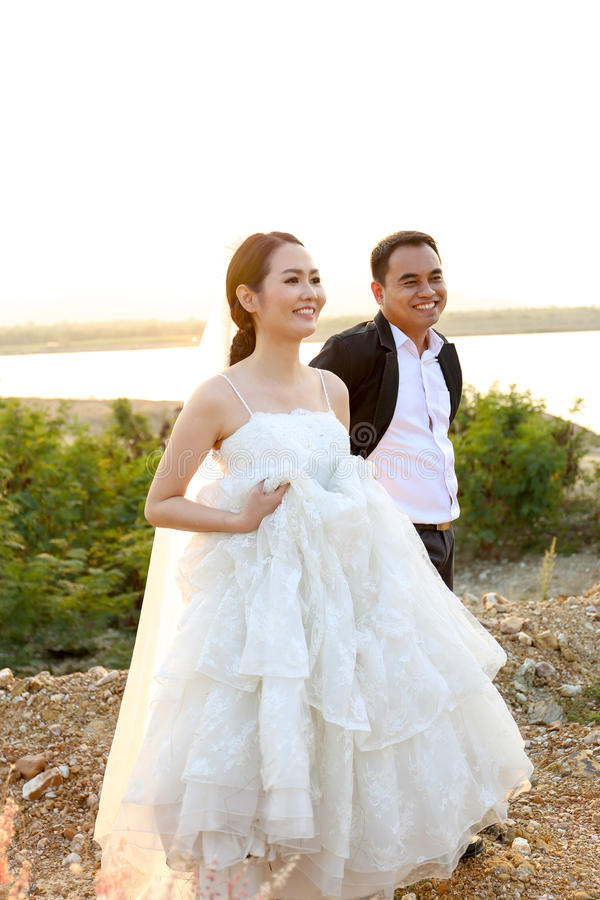 Asian Bride And Groom In Wedding Dresses Against The Sunset Scene