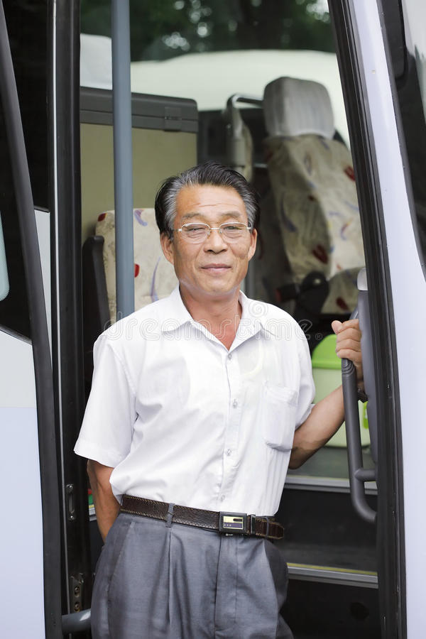 Asian bus driver. Elderly Asian bus driver with his bus stock photography