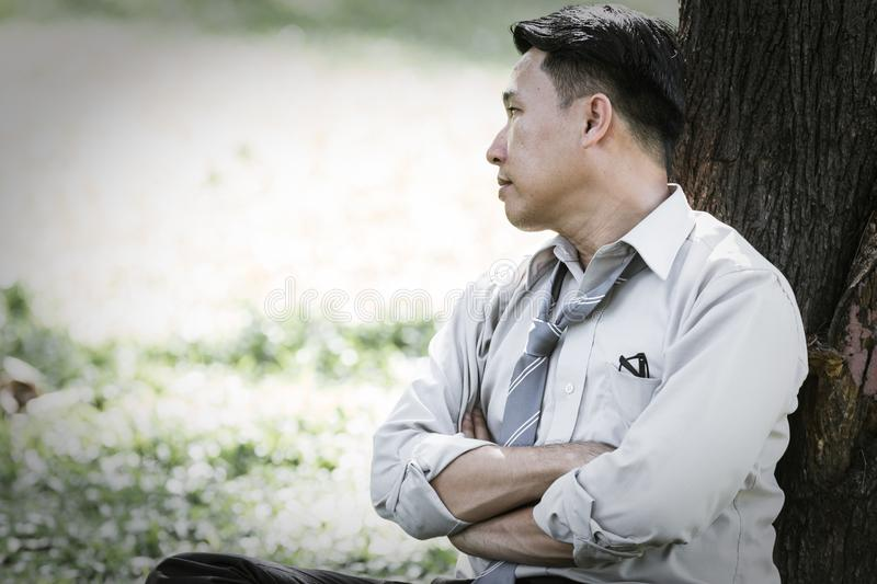 Asian business man. Failing and serious under tree in the park royalty free stock photo
