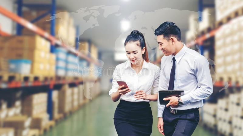 Asian Business man and Business woman worker in warehouse using stock photos