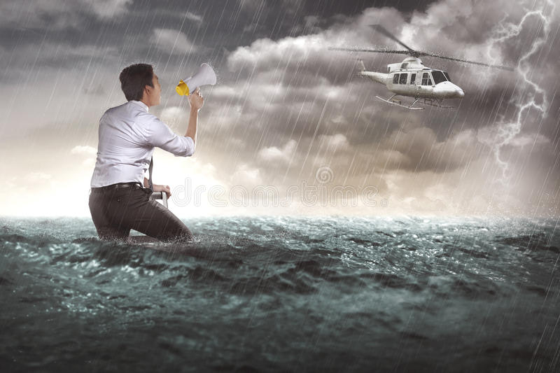 Asian business man calling help with bullhorn. He lost in the sea stock photography