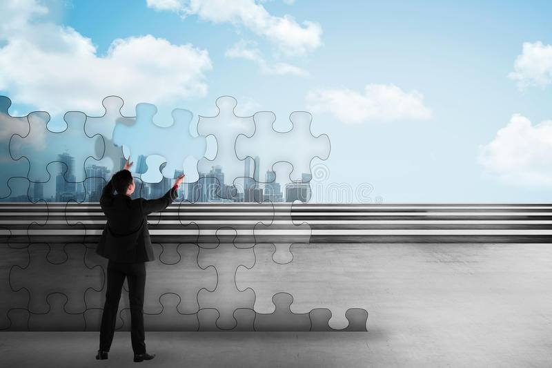 Asian business man holding piece of puzzle trying to build a city stock image