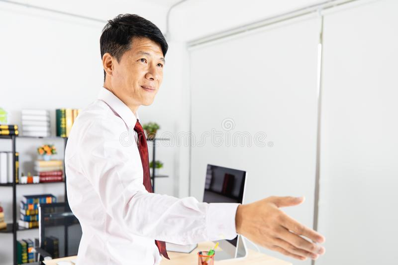 Asian business man isolated white. Close up portrait of middle aged, handsome, Asian, businessman, in white shirt, necktie, black pants posing handshake sign for royalty free stock photography