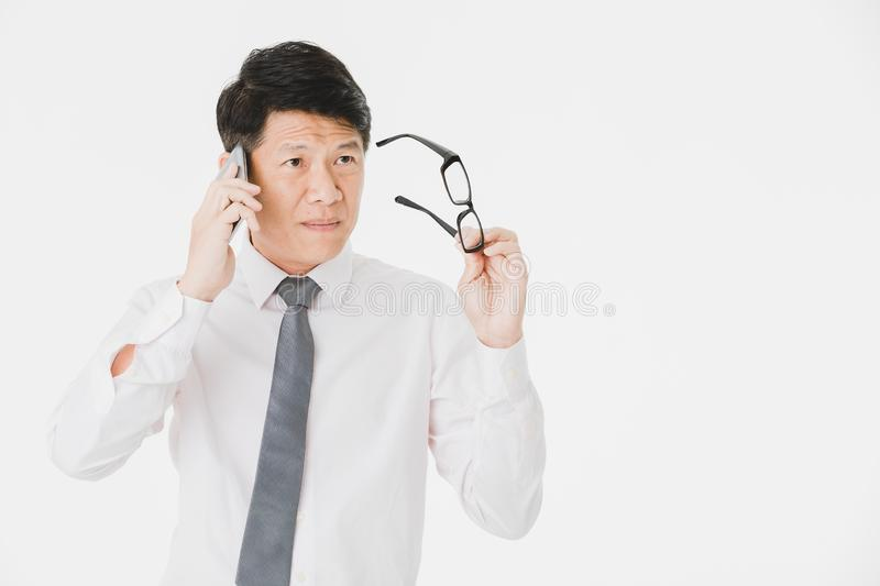 Asian business man isolated white. Close up portrait of middle aged, handsome, Asian, businessman, in white shirt, striped tie.posing, holding smartphone and royalty free stock photo