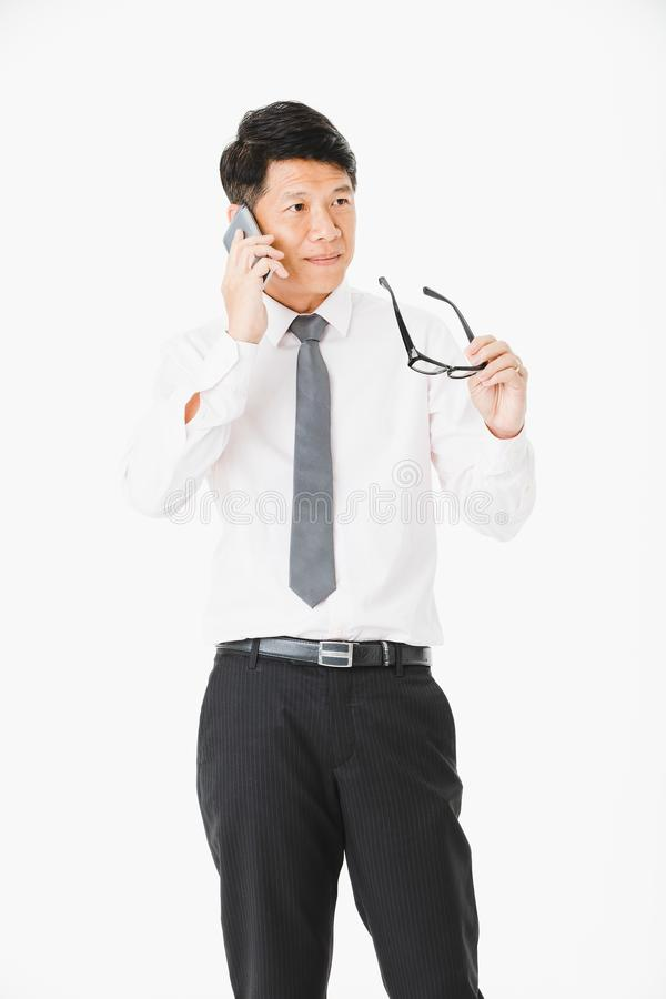 Asian business man isolated white. Close up portrait of middle aged, handsome, Asian, businessman, in white shirt, striped tie.posing, holding smartphone and royalty free stock images