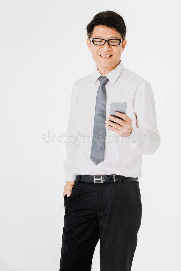Asian business man isolated white. Full length portrait of middle aged, handsome, Asian, businessman, in white shirt, striped tie.black pants and shoes, wearing royalty free stock photo