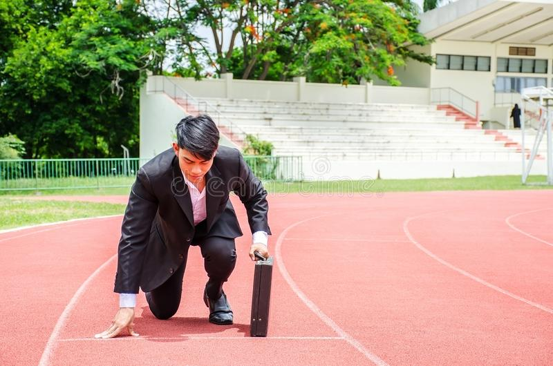 Asian business man kneeling on the starting grid of a running track stock photos