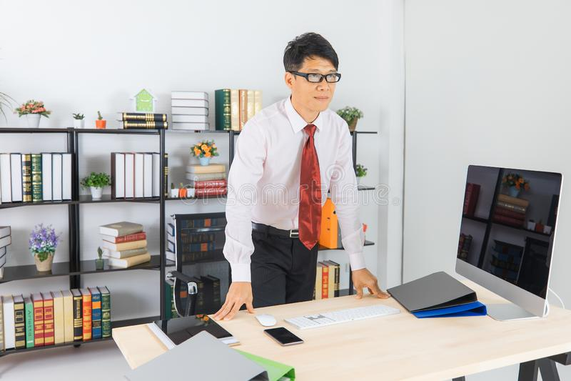 Asian business man at office. Close up portrait of middle aged, handsome, Asian, businessman, in white shirt, dark red necktie, standing at the desk in the stock image
