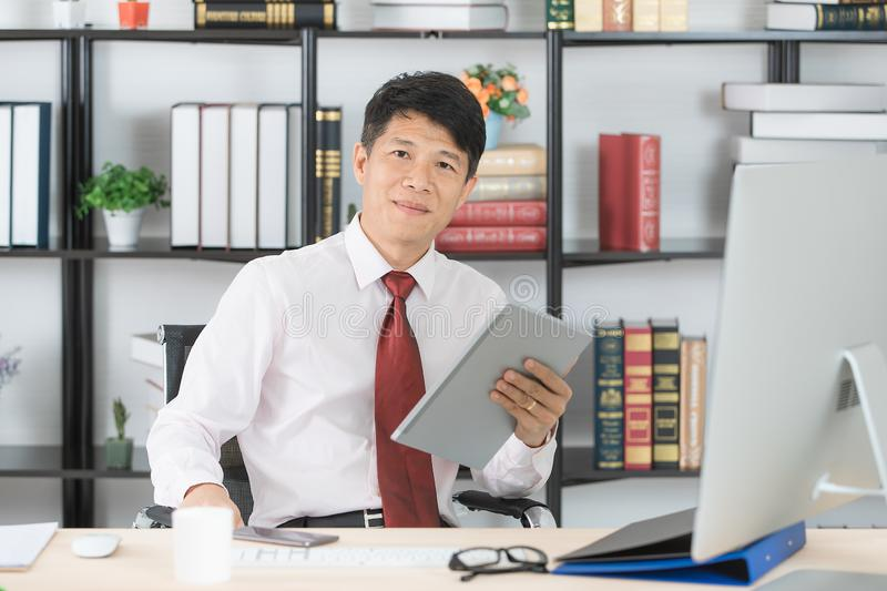 Asian business man at office. Middle aged, handsome, Asian, businessman, in white shirt, dark red necktie, browsing data in tablet, in his startup office, with royalty free stock photo