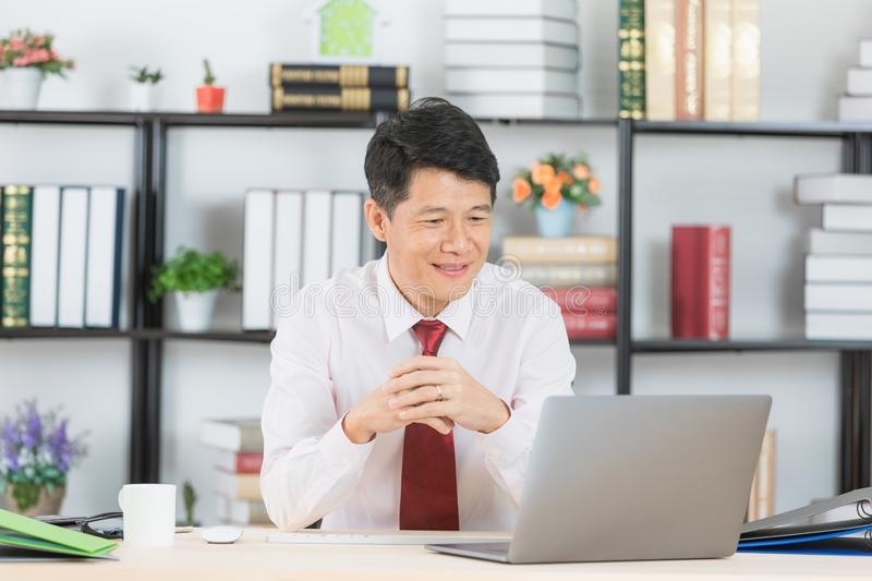 Asian business man at office. Middle aged, handsome, Asian, businessman, in white shirt, dark red necktie, sitting in his startup office, crossed hands, posing stock photos