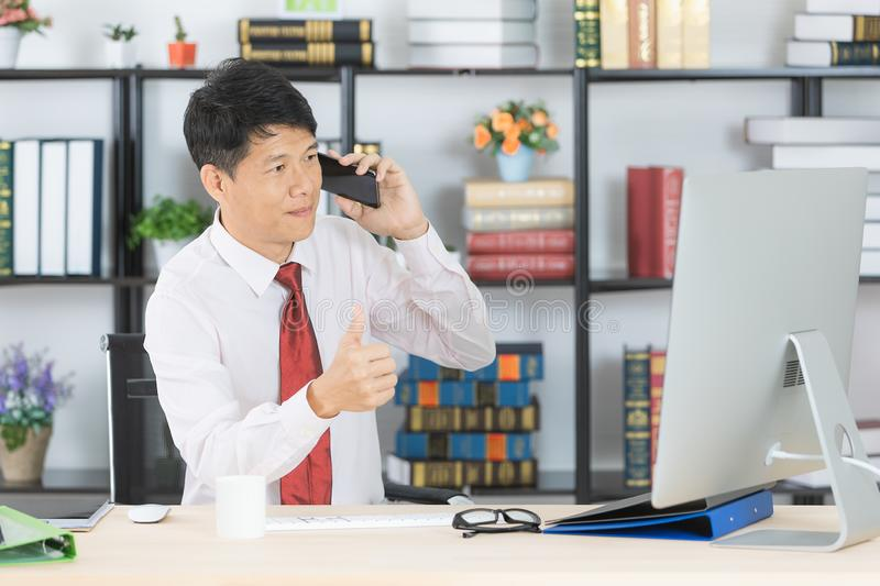 Asian business man at office. Middle aged, handsome, Asian, businessman, in white shirt, dark red necktie, talking with customer on smartphone, in his startup royalty free stock photos