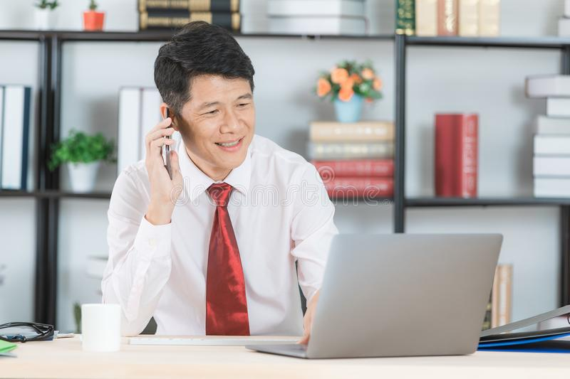 Asian business man at office. Middle aged, handsome, Asian, businessman, in white shirt, dark red necktie, working in his startup office, holding smartphone stock images
