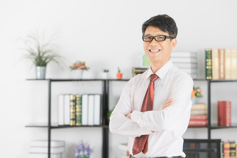 Asian business man at office. Portrait of middle aged, handsome, Asian, businessman, wearing eyeglasses, in white shirt, dark red necktie, posing in front of his stock photos