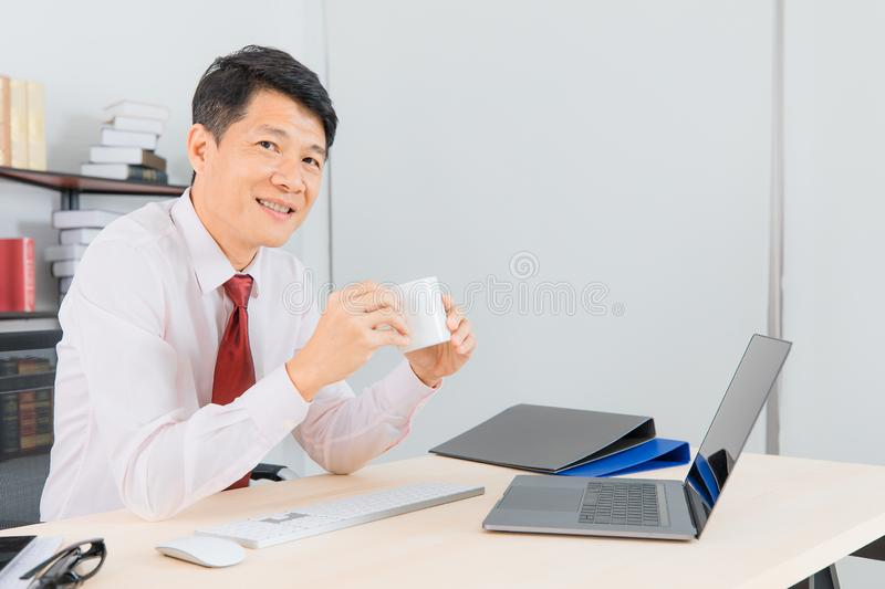 Asian business man at office. Portrait of Middle aged, handsome, Asian, businessman, in white shirt, dark red necktie, working in his startup office, happy with royalty free stock photos