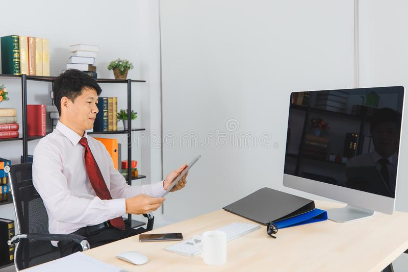 Asian business man at office. Portrait of Middle aged, handsome, Asian, businessman, in white shirt, dark red necktie, working in his startup office, happy with stock photo