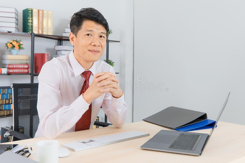 Asian business man at office. Portrait of Middle aged, handsome, Asian, businessman, in white shirt, dark red necktie, working in his startup office, happy with stock image
