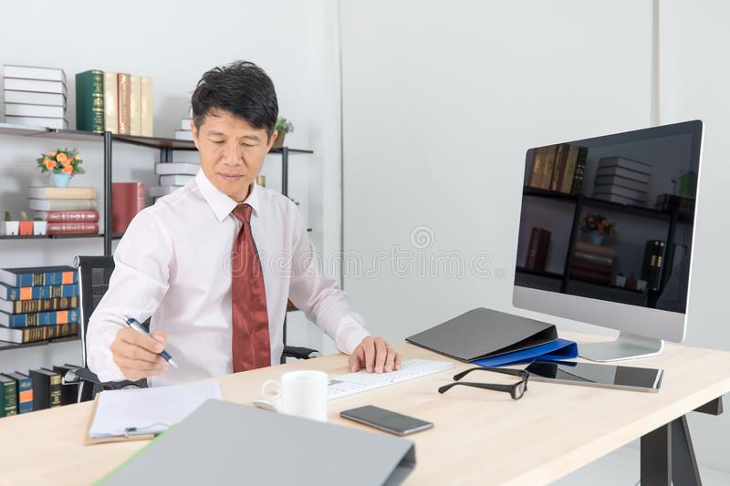 Asian business man at office. Portrait of Middle aged, handsome, Asian, businessman, in white shirt, dark red necktie, working in his startup office, happy with royalty free stock photo