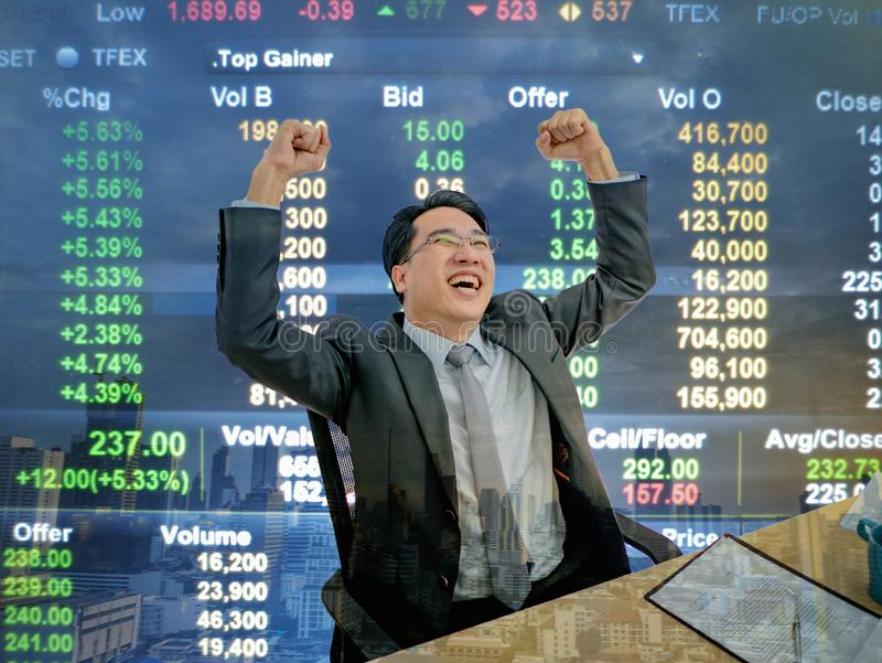 Asian business man sitting very happy becuase his stock market g. Rowth up,business man sitting on his desk with stock market background,business concept royalty free stock images
