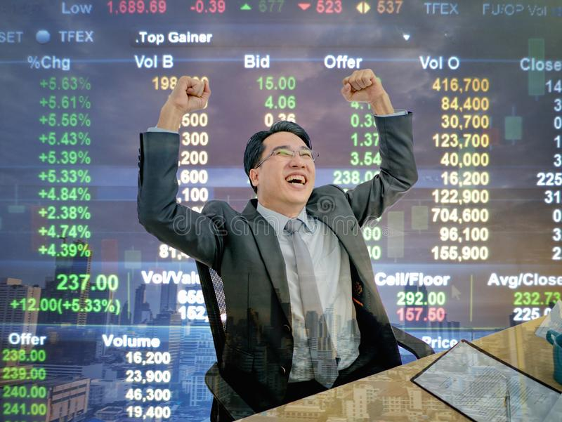 Asian business man sitting very happy becuase his stock market g. Rowth up,business man sitting on his desk with stock market background,business concept royalty free stock photography