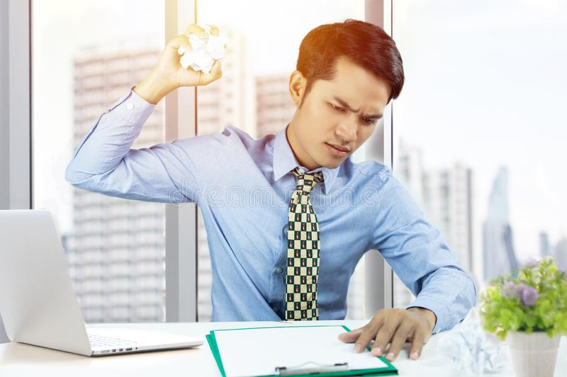 Asian business man throwing paper and serious about the work done until the headache stock photography