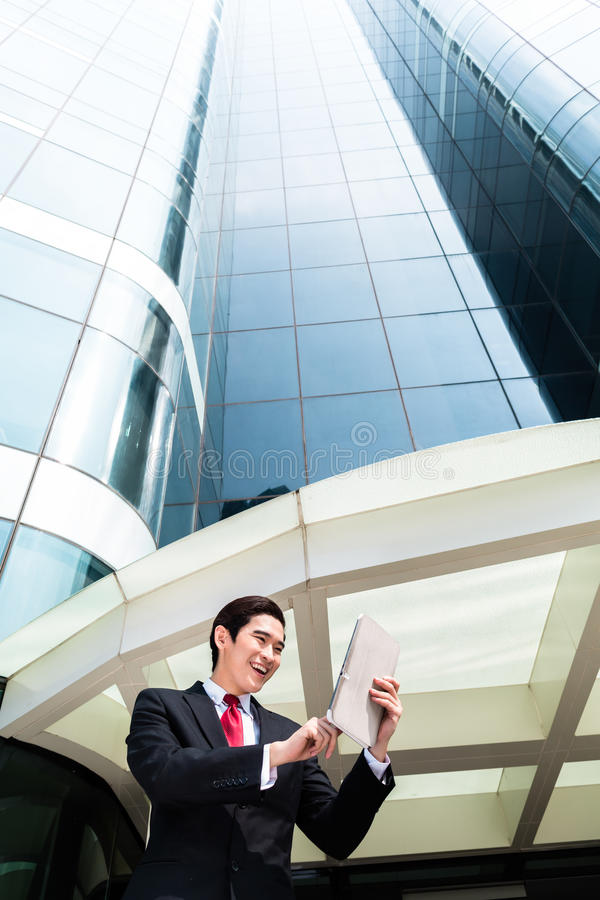 Asian business man working outside on tablet PC royalty free stock photos