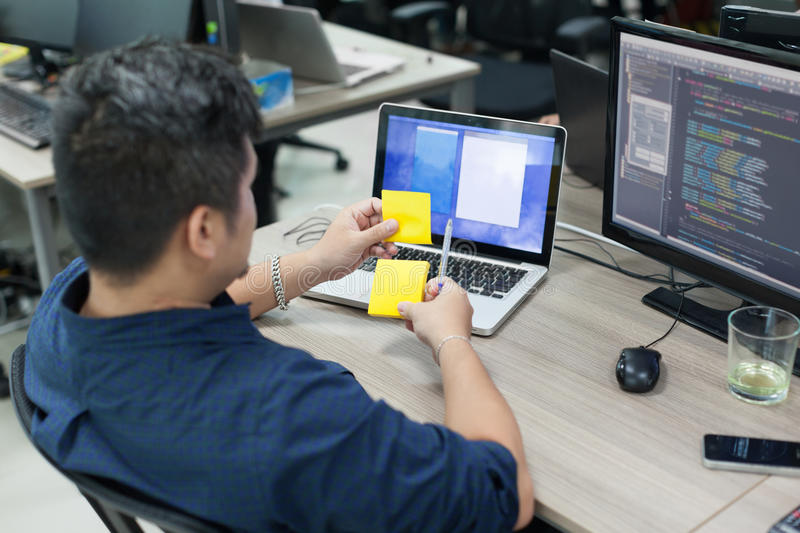Asian business man yellow sticky note, rear back. View thinking idea computer developer working desk laptop sitting real office stock images