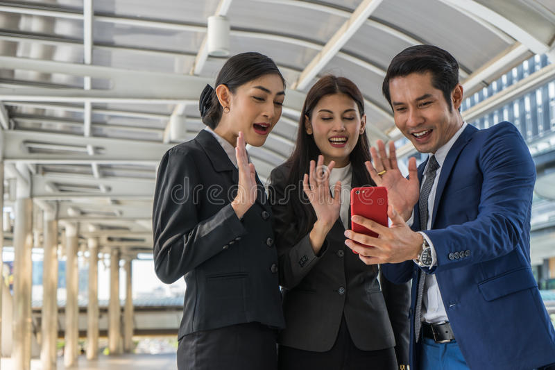 Business man and business woman doing conference call with someone on mobile phone. Asian business men and business women doing conference call with someone on stock image