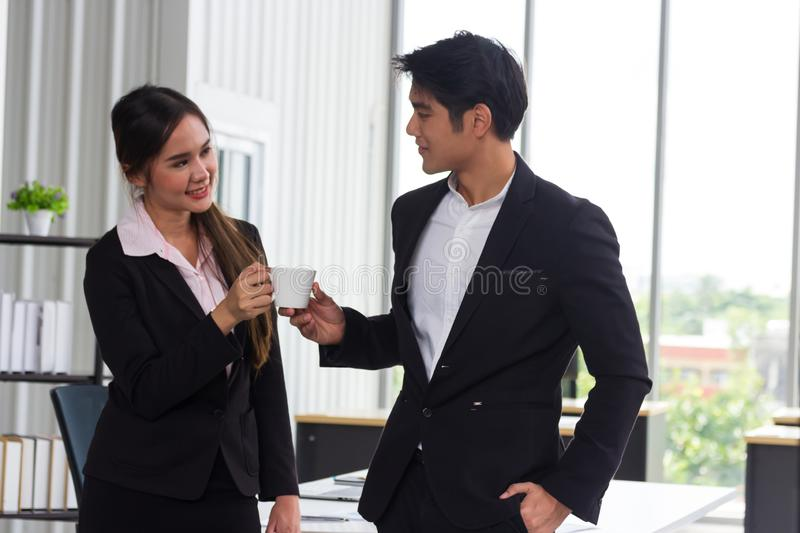 Asian business men and women Holding a white coffee cup during the break. royalty free stock image