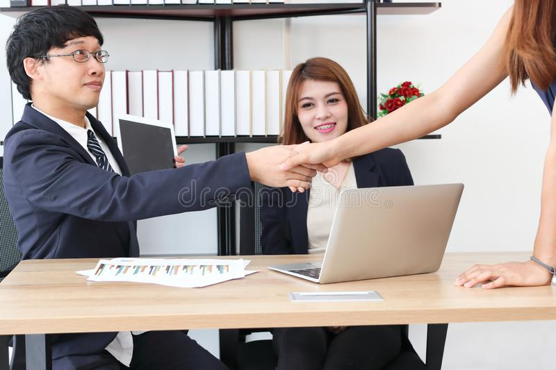 Asian business partners shaking hands after successful deal stock images