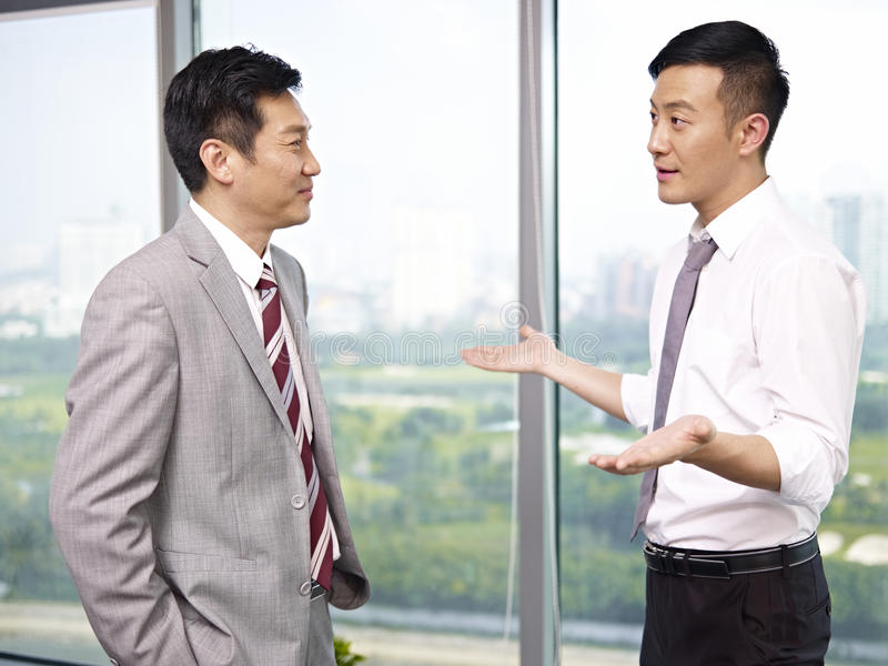 Asian business people. Asian businessman standing and talking in office royalty free stock photos