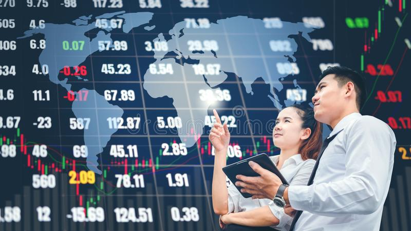 Asian business people meeting and working on digital tablet Stock market exchange information and Trading graph background.  royalty free stock images