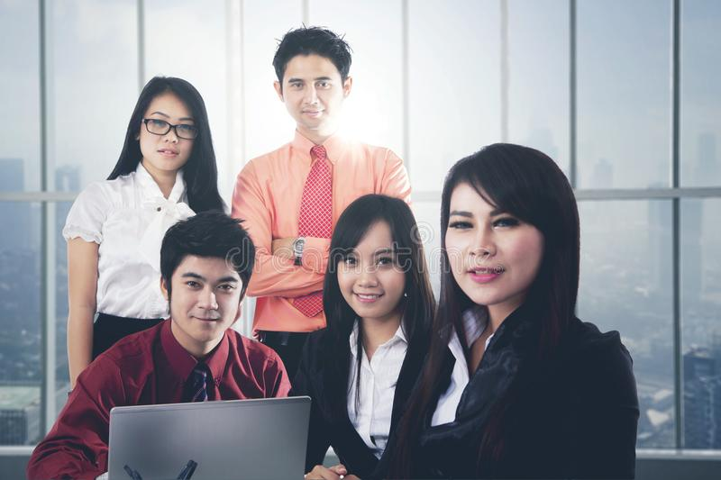 Asian business people in a modern office. Confident Asian business people with laptop posing together in modern office royalty free stock photos