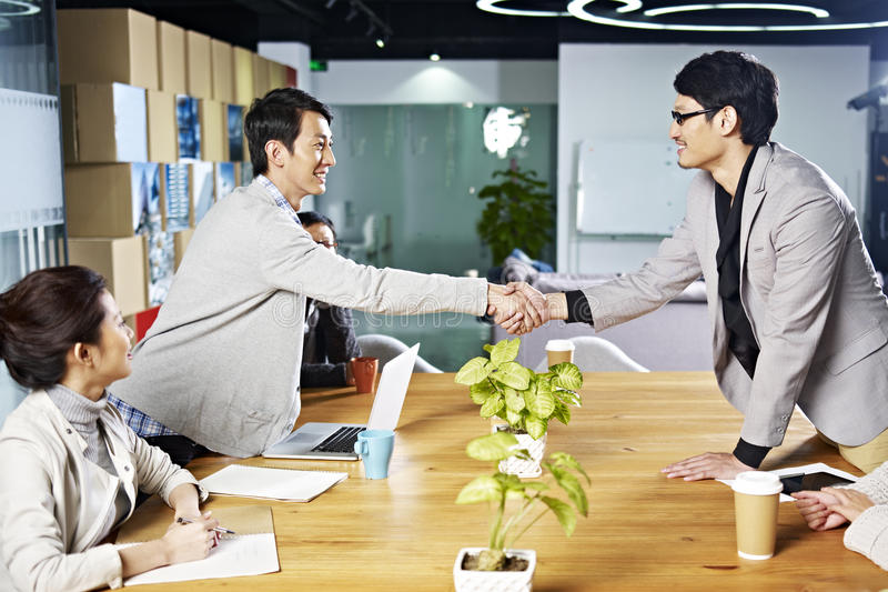 Asian business people shaking hands royalty free stock image