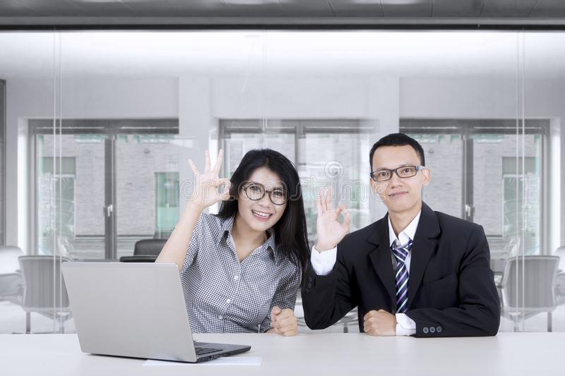 Asian business people showing OK sign. Two young successful Asian business people showing OK sign with a laptop on desk in the office room stock photos