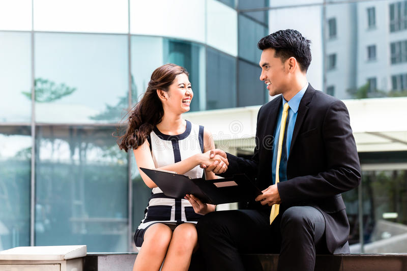 Asian business people working outside on documents stock photography