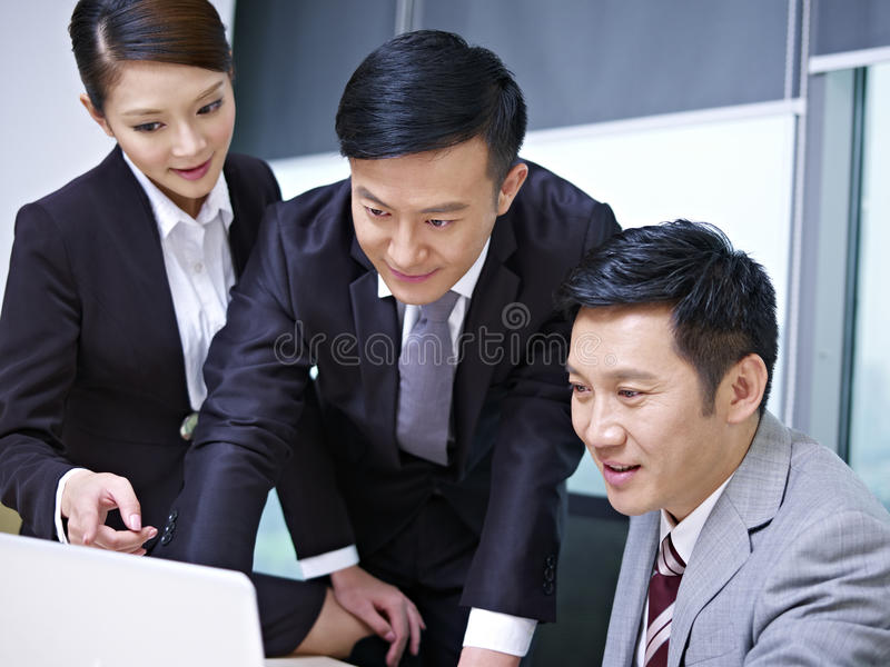 Asian business team. A team of asian business people working together in office royalty free stock photo