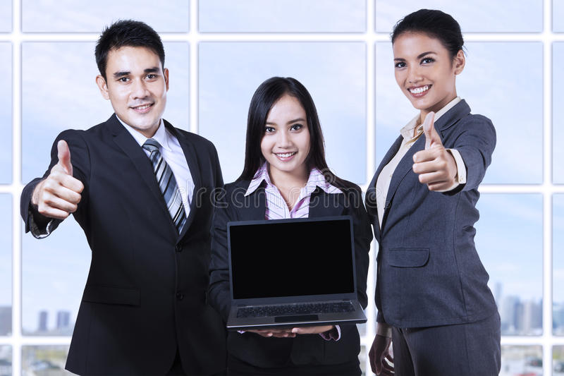 Asian business team showing blank screen on laptop royalty free stock photos
