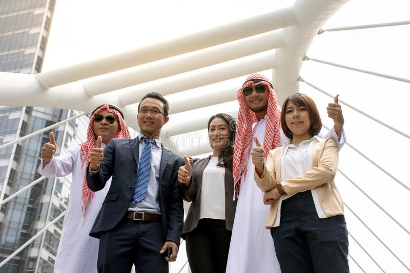 Asian business team showing thumb up for good work with city background stock photography