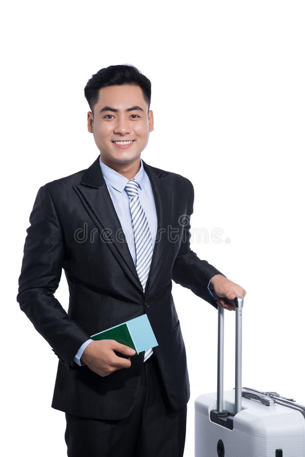 Asian business traveler pulling suitcase and holding passport an royalty free stock photos