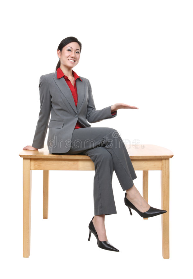 Asian Business Woman. A pretty asian business woman sitting on a table stock photography