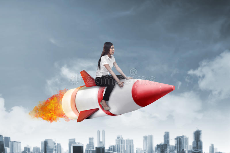 Asian business woman flying ride rocket. Image of asian business woman flying ride rocket royalty free stock photo