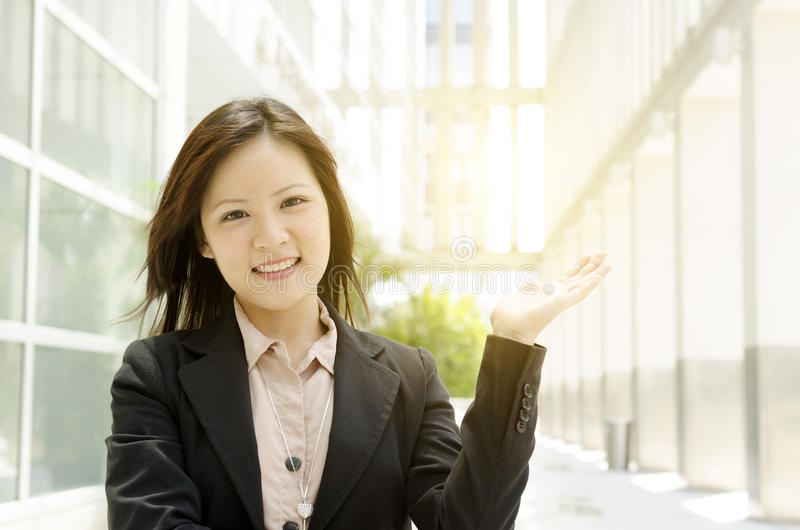 Asian business woman hand holding somethings. Young Asian business woman hand showing somethings, at an office environment, natural golden sunlight at background stock photos