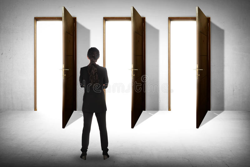 Asian business woman has to choose doors. Asian business woman has to choose between three options royalty free stock photo