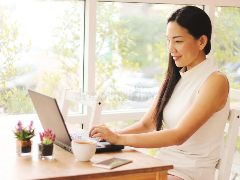 Asian business woman with long black hair working in coffee shop , typing on computer royalty free stock photo